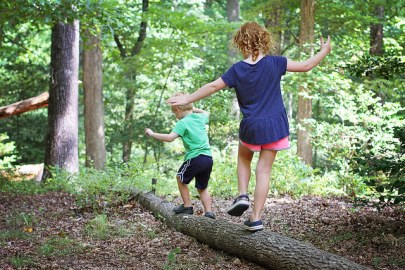 Two white children run along a fallen log.
