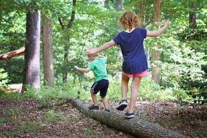 Two white children run along a fallen log.