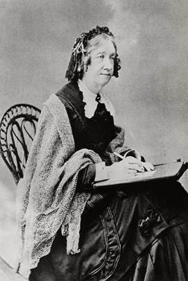 Photograph of a white woman sitting with a writing slate in her lap, wrapped in a shawl and with a shaggy curly hairdo.