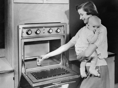 Photo showing a woman holding a baby preparing to heat food in a Tappan microwave oven