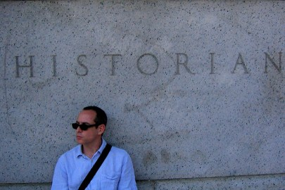 """A white man in sunglasses sits beneath a granite sign that has """"HISTORIAN"""" engraved in it."""