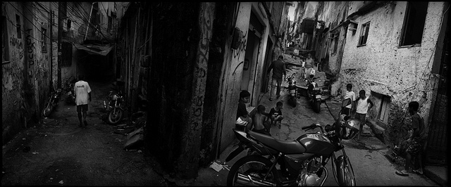 Landscape black and white photo of an alleyway in Rio de Janeiro, Brazil. Young people sit on the curb, a motorcycle is at the fore.