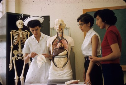 Three indigenous women stand around an anatomical model. One woman wears a nurses uniform.