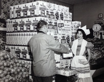 Black and white photo of a white woman in a Dutch costume handing a white man a box of Old Dutch chips.