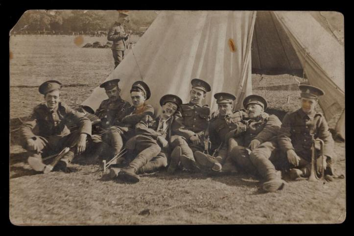 Soldiers lay in front of a tent.