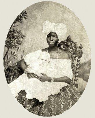 A black nanny with a white child.