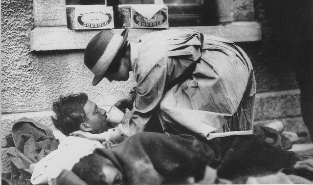 A white lady in a bomb ass hat bends over a man and cradles his head as she holds a glass to his lips