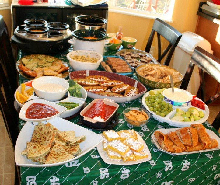 A football field table cloth is laden with an assortment of snacks, including lemon bars, veggies with dip, fruits with dip, quesadillas, chicken slices?, and other edibles.