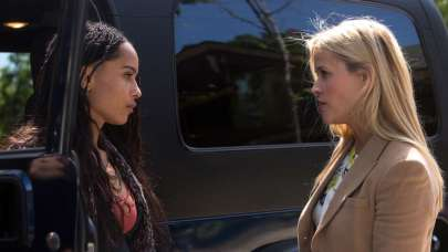 Zoe Kravitz and Reese Witherspoon face eachother next to a blue Jeep, talking.