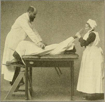 A creepy bearded white guy stands on a short ladder to be at hip height to a table on which a woman is laid out with her legs spread. He had his hands on her hips, and a nurse holds her arms at a 45 degree angle from the patient's head.