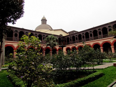 Photograph of the courtyard of a Spanish-style convent. There are short trees in the foreground, and a dome in the background.