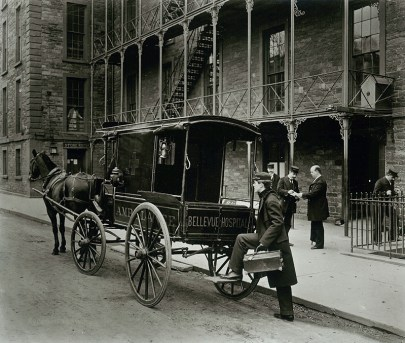 Black and white photo of a horse-pulled carriage with the words Bellevue Hospital written across the side. It is parked outside a building, and there are men in servant uniforms and one man carrying a doctor's case milling around it.