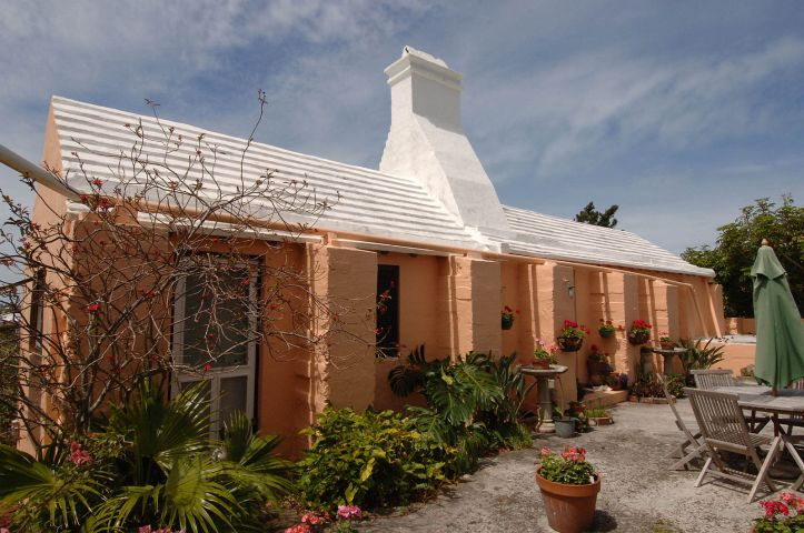 Photo of a peach-painted stone building with a white roof. There is a nice little garden in front of the building.