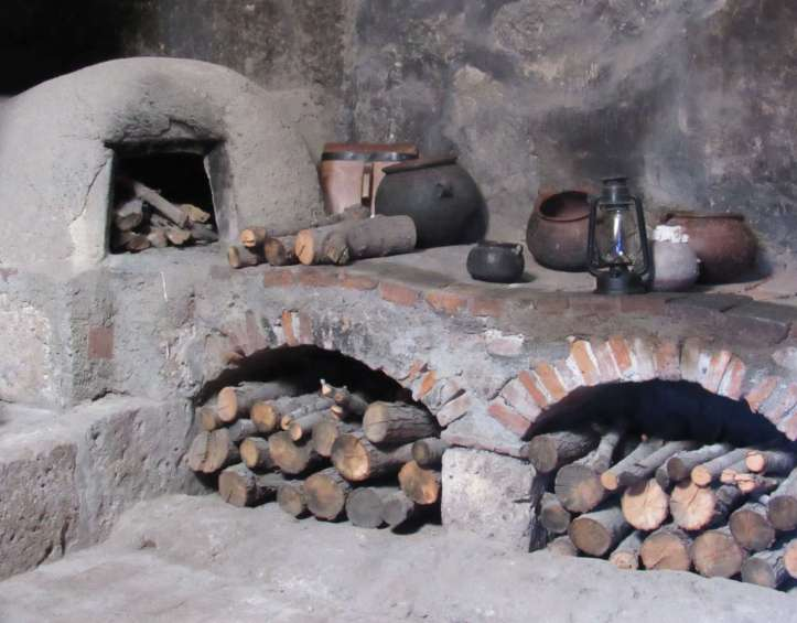 Photo of an old kitchen made of adobe and brick with a wood oven and two wood storage spaces.