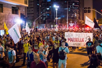 "A crowd marches in the streets of Rio, and some people hold up a sign that says ""Quem Matou Marielle?"""