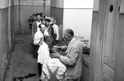 Black and white photo of two barbers shaving the heads of two other seated men while others look on.