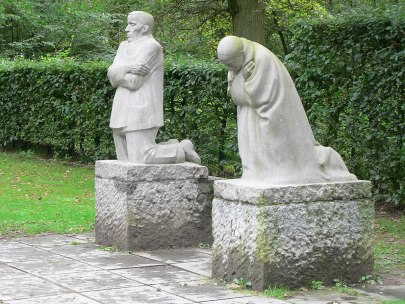 Two statues showing a mother figure kneeling and bowed over, her face obscured, and a father figure also kneeling looking up and out, his gaze falling on the grave of Kollwitz's son Peter, who was killed in battle in 1914.