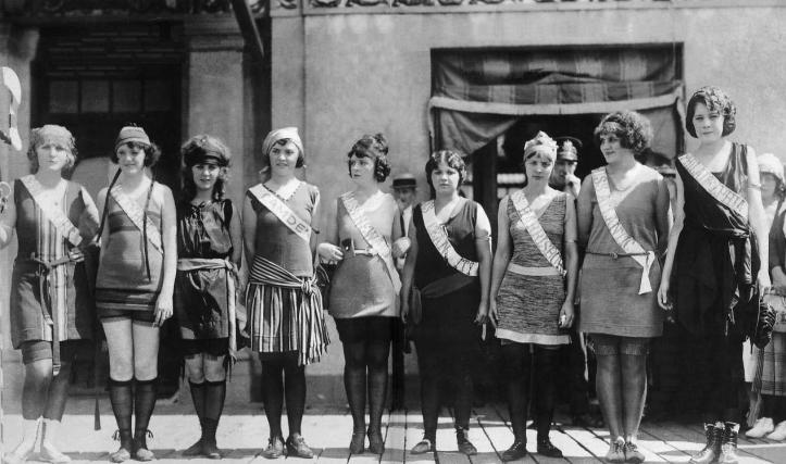Nine women standing in a line side-by-side all wearing 1920s-era swimsuits, all wearing sashes with different US cities or states written on them.