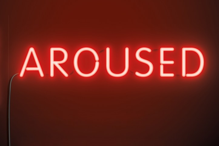 "Detail of a book cover showing red glowing neon lettering saying: ""Aroused"" in all capital letters."