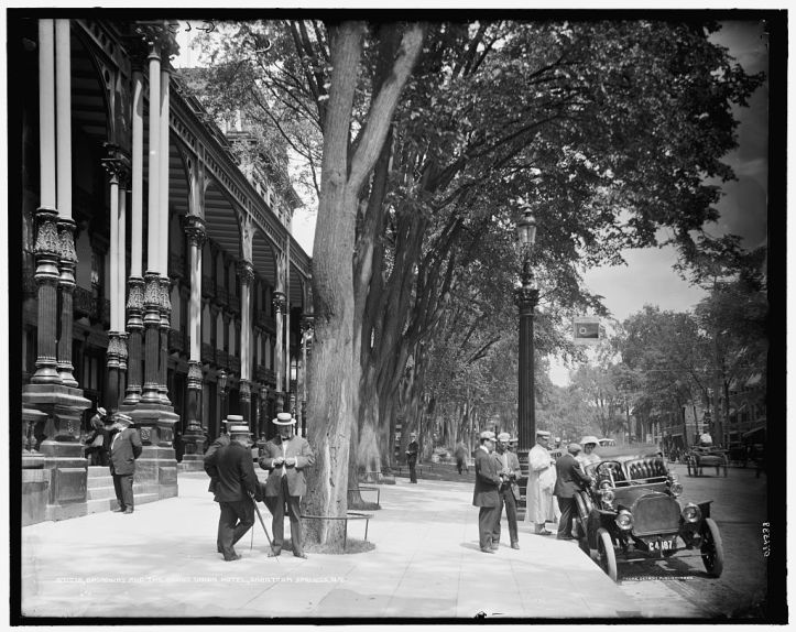 An early twentieth century US street scene with a very wide sidewalk, people in straw hats standing and talking, and a line of columned buildings.
