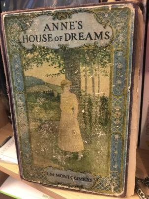 A worn copy of the book Anne's House of Dreams, with an illustrated cover showing a woman in a yellow dress standing next to a large tree.
