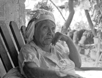 An older woman wearing a white cap sits in an adirondack chair.
