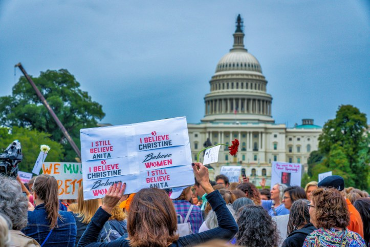A large crowd of protesters in front of the US Capitol building in Washington DC. A prominent sign in the foreground reads: I still believe Anita, I believe Christine, Believe Women.