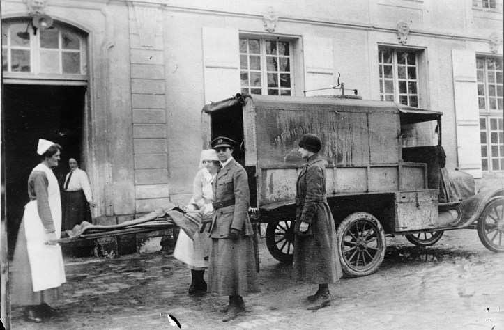 Two women loading a stretcher into a WWI-era truck with two other people standing in the foreground.