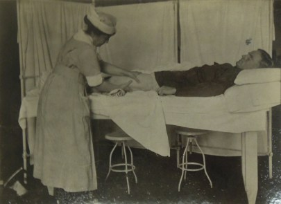A person laying on a medical bed while a standing person in medical robes massages their thigh.