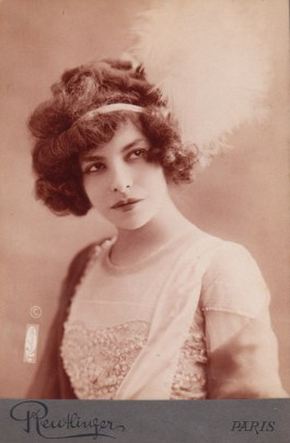 A sepia-toned soft-focus portrait of a young woman in an embroidered top with a curly up-do.