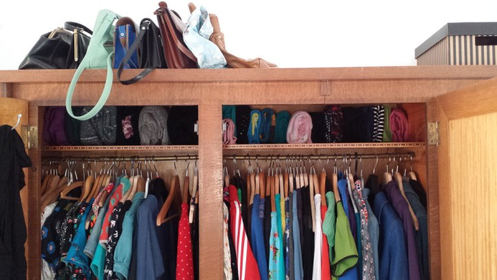 A brown wood closet interior, with purses stacked on a top shelf, shoes lining a smaller interior shelf, and shirts and pants hanging on hangers.