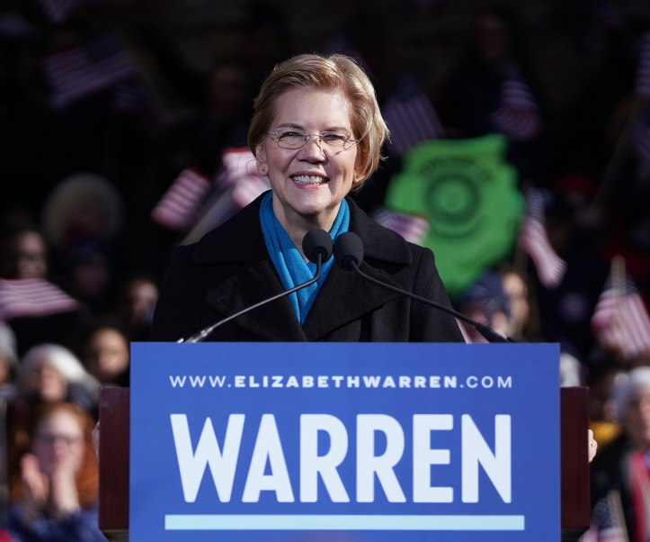 "Elizabeth Warren standing behind a podium and microphone in a black jacket and teal scarf, a campaign sign declaring ""WARREN"" in large text and ""www.elizabethwarren.com"" in smaller text. There is a crowd of people behind her."