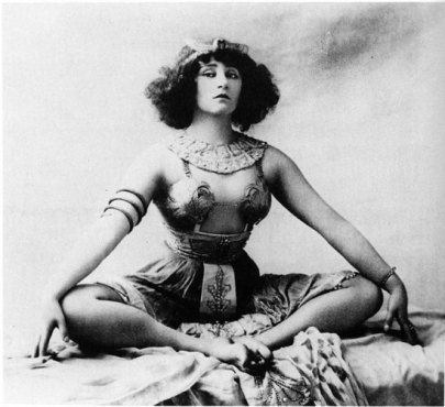 A woman in a stylized Egyptian costume sitting with legs apart and feet together with her wrists resting on her knees.