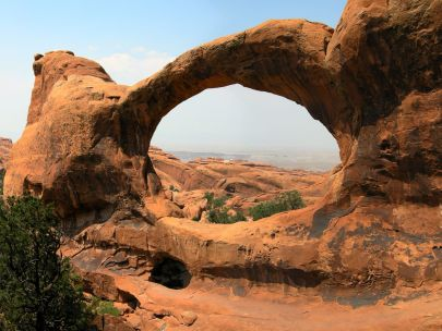 A rock formation in a sandy reddish hue forms a arch in the desert.