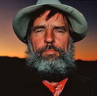 Headshot of Edward Abbey with a bushy gray beard, a tan wide-brimmed hat, and ared bandana. Behind him is a desert sunset