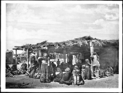 Photograph of a group of more than 30 Mojave Indians mourning over the body of their dead chief, Sistuma, standing or sitting under the thatched porch roof in front of a small dwelling with a thatched roof. Many of them are wearing blankets draped about their shoulders. Other dwellings are visible behind.