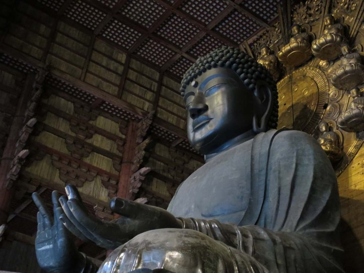 A large seated statue of the Great Buddha, with its eyes closed and one hand palm up the other palm out. In an ornate wood-walled enclorsure with gold smaller buddha statues arranged in a circle behind it.
