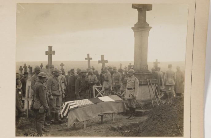 A group of soldiers in WWI uniforms standing around a flag-draped coffin among tall cross-topped grave stones.