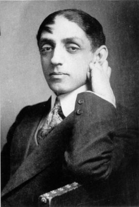 Photo of Mikhail Kuzmin, a Russian man with heavy lidded eyes, sitting with one hand positioned just beneath his ear. Wearing a 3 piece suit
