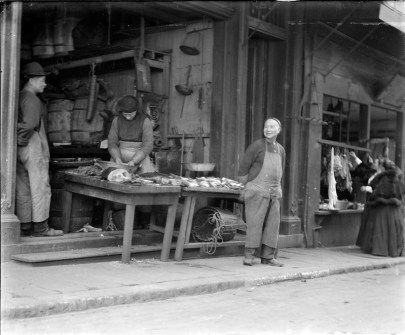 A Chinese man stands in front of a table of fish outside.
