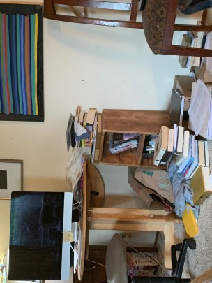 Photo of an office, with stacks of books on the floor and desk, a desktop computer monitor in the left of the photo, a chair in the right of the photo, and a wall with some colorful artwork hanging. Papers are also scattered in the foreground.