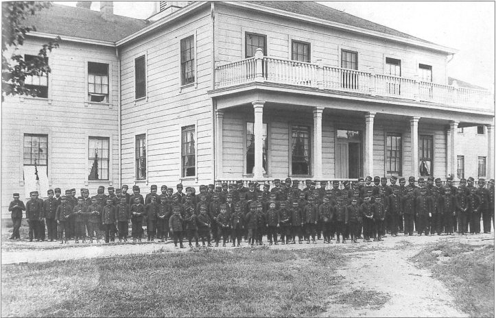 Rows of dozens of Native American boys in little soldiers uniforms that look sort of like Union Soldiers, ages ranging from five to thirteen or so, stand in front of a big white house with a columned balcony on the front.