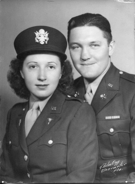 The Lowderbacks are pictures in their military uniforms, smiling a little bit. Both are white, Charlie is a little taller than Ruth in the image.