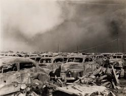 1940s-era cars are parked bumper to bumper and burned out, windows missing, metal of the frame collapsing in on itself. There's also a thick white smoke cloud hanging in the air