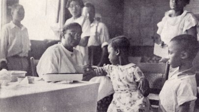 a woman with short cropped hair and glasses immunizes a little girl in a pretty flowered dress as part of the Smith College chapter of Alpha Kappa Alpha's summer health clinic