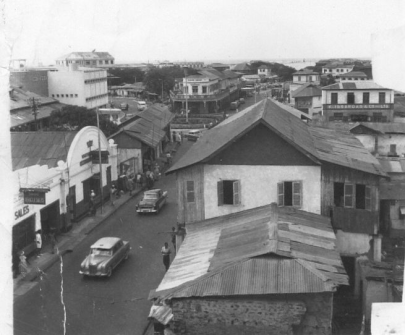 Black and white photo of a neighborhood in Accra, Ghana. Seems to be from a rooftop overlooking a street and several other small houses.