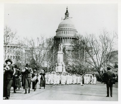 Photo of the street outside the capitol building; a group a women in white march; more women dressed in dark colors are marching in front of them