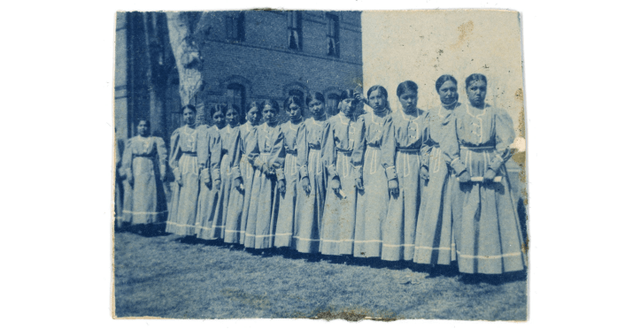 Two dozen teenaged girls, labeled as Crow Indians, stand in a row in identical dresses in front of a two or three story building, one of Montana's Indian Boarding Schools