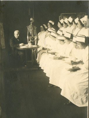 A man writes on a piece of paper at a desk. Two rows of nurses in white uniforms take notes.
