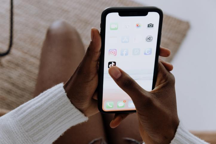 A pair of hands with darker skin tone holds an iPhone. One thumb is poised to click on the TIkTok app.